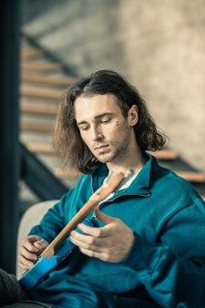 Ripetizione musicale. giovane uomo di bell'aspetto incurante che intona le corde della sua chitarra mentre si rilassa nel soggiorno