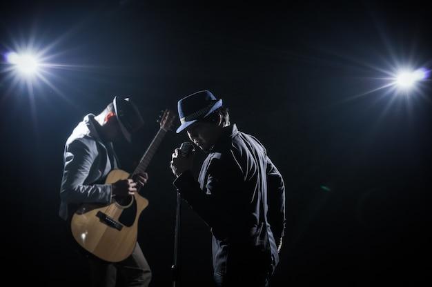 Musicista duo band mano che regge il microfono e canta una canzone e suona la chitarra su bac nero