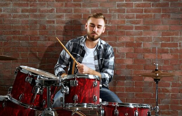Musicista che suona la batteria sulla priorità bassa del muro di mattoni