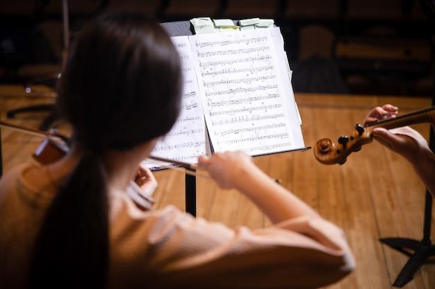 Musicista che suona il violino e legge lo spartito durante il concerto di musica classica