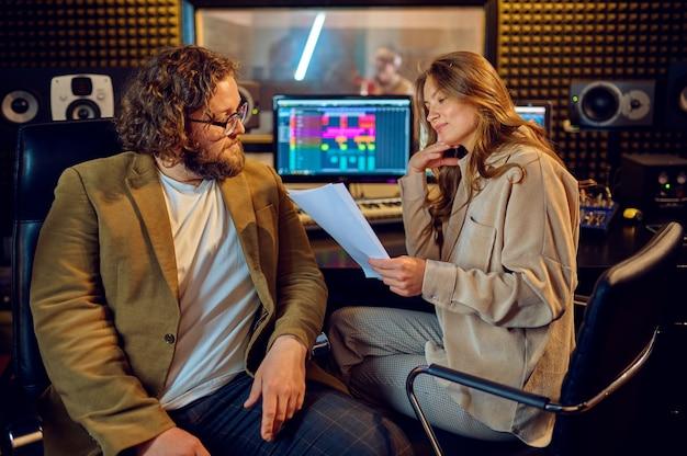 Musicisti alla console di mixaggio, interni dello studio di registrazione sullo sfondo. sintetizzatore e mixer audio, posto di lavoro del musicista, processo creativo, registrazione di brani