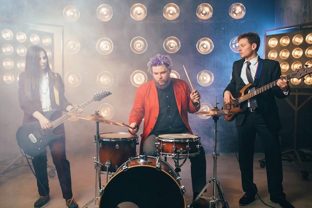 Musicisti in giacca e cravatta sul palco con luci, stile vintage. chitarristi e batterista, concerto rock band, spettacolo musicale