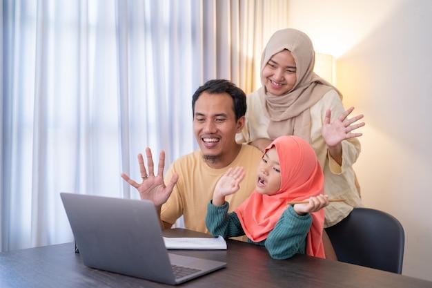 Mano d'onda della famiglia asiatica musulmana durante la videochiamata utilizzando il tablet con un amico