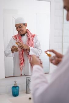 Uomo asiatico musulmano che si prepara per eid mubarak. vestirsi e applicare il profumo al suo corpo