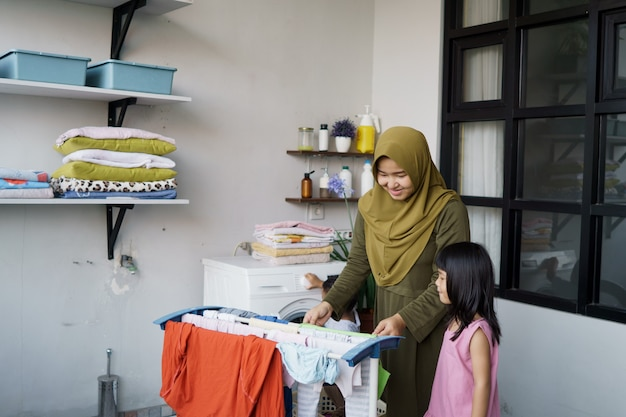 Madre asiatica musulmana e bambina piccola aiutante in lavanderia vicino alla lavatrice