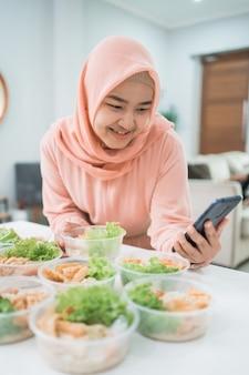 Servizio di catering domestico della donna asiatica musulmana che prepara il pranzo al sacco per l'ordine online di cibo da asporto