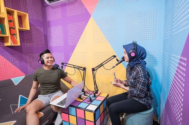 Uomo e donna asiatica musulmana che parlano insieme in studio podcast