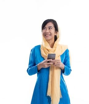 Donna asiatica musulmana che pensa e che tiene telefono
