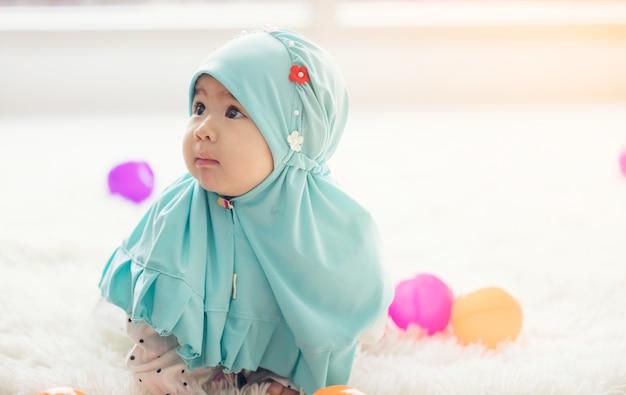 Il bambino musulmano gioca con i giocattoli colorati nel soggiorno.