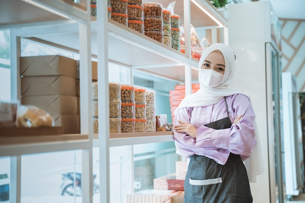 Imprenditore musulmano con maschera in attesa del cliente in piedi accanto alla vetrina del suo negozio durante l'apertura nella nuova normalità