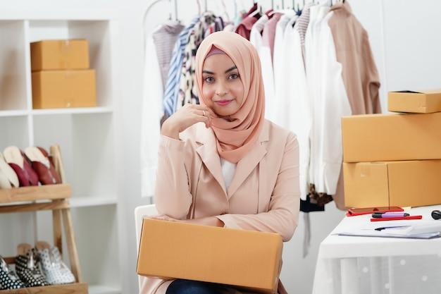 Donna d'affari musulmana che vende prodotto online.