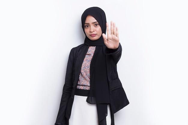 Donna d'affari musulmana con la mano aperta che fa il segnale di stop con un gesto di difesa dell'espressione seria