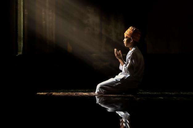 I bambini musulmani scherzano gli uomini che indossano camicie bianche facendo il libro di lettura della preghiera