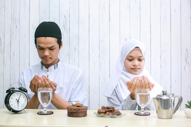 Coppia musulmana che prega insieme al momento dell'iftar con foto di messa a fuoco selettiva sulle mani in preghiera