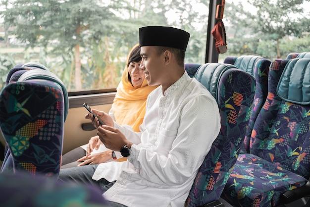 Coppia musulmana viaggia in autobus durante le vacanze di eid mubarak per incontrare la famiglia a casa