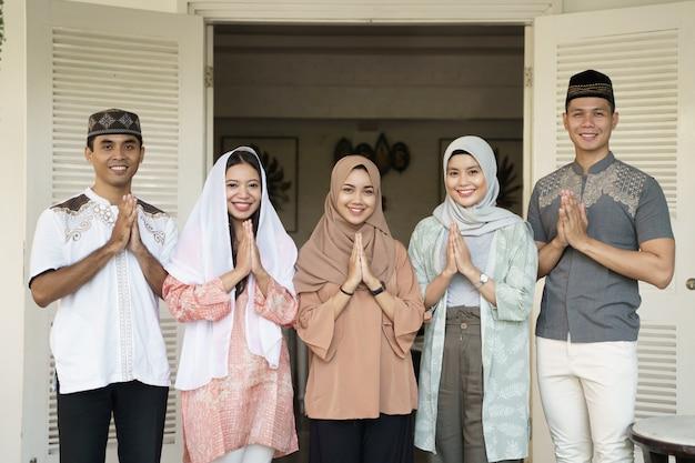 Famiglia musulmana e amico saluto guardando la fotocamera
