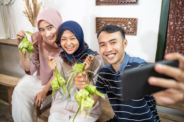 Famiglia musulmana e amico che preparano la torta di riso ketupat a casa usando foglie di palma per eid fitr