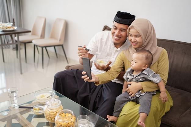 Famiglia musulmana che prende insieme selfie