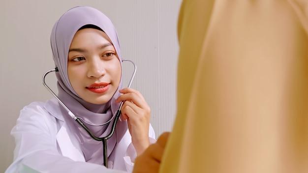 Medico femminile musulmano che controlla sulla salute del paziente alla stanza di ospedale.