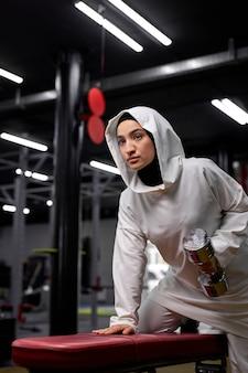 Donna musulmana in forma facendo esercizi con manubri, donna araba concentrata sull'allenamento, sta guardando di lato, tenendo in mano un peso elevato