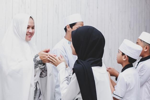 Amico musulmano e famiglia che si stringono la mano e si perdonano durante la celebrazione di eid mubarak
