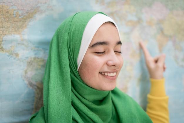 Ragazza musulmana con mappa del mondo