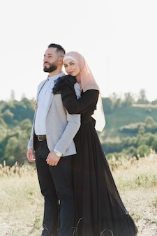 Primo piano musulmano di storia d'amore coppia mista sorrisi e abbracci sulle verdi colline.