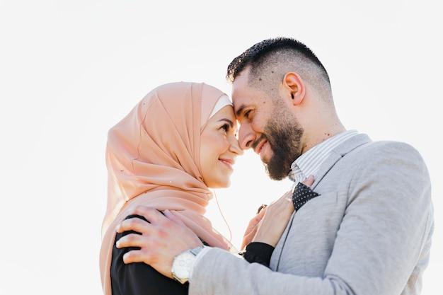 Primo piano musulmano di storia d'amore con la luce del sole coppia mista sorrisi e abbracci al tramonto.