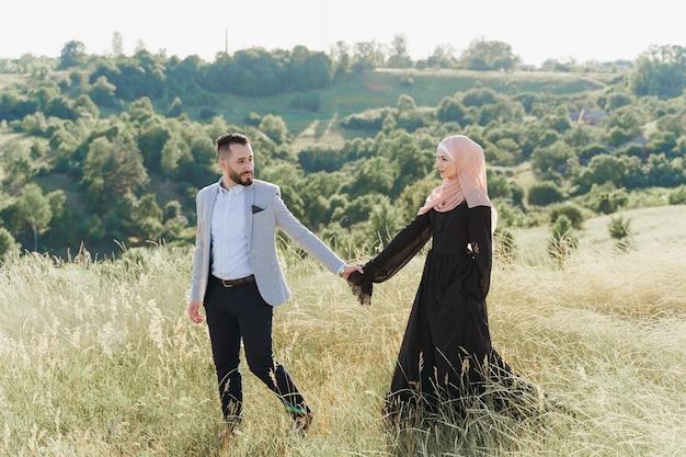 Storia d'amore musulmana di una coppia mista. l'uomo e la donna sorridono e camminano sulle verdi colline.