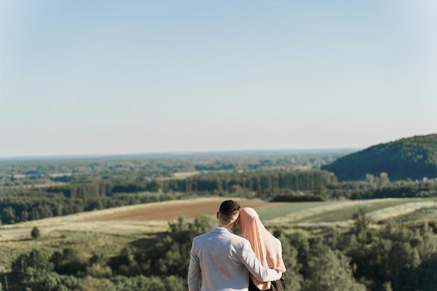 Storia d'amore musulmana. coppia mista sorrisi e abbracci sulle verdi colline.