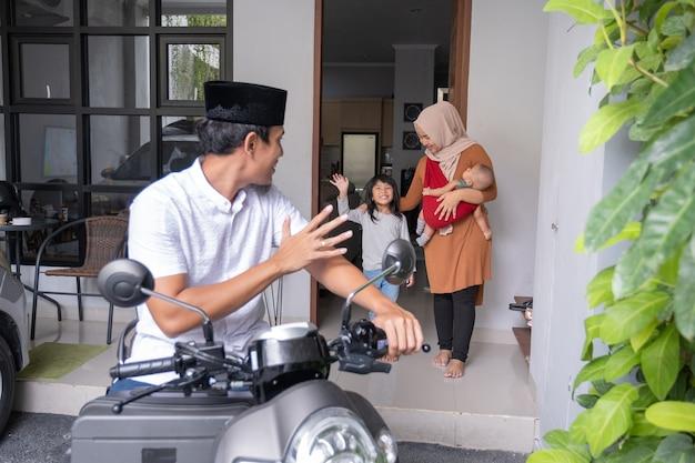 Uomo musulmano che va in scooter lasciando la sua famiglia a casa