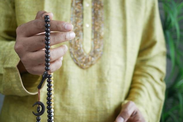 L'uomo musulmano tiene la mano nei gesti di preghiera durante il primo piano del ramadan