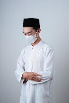 Uomo musulmano che prega contro su grigio con maschera facciale
