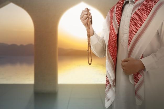 Uomo musulmano che prega con i grani di preghiera sulle sue mani sulla moschea