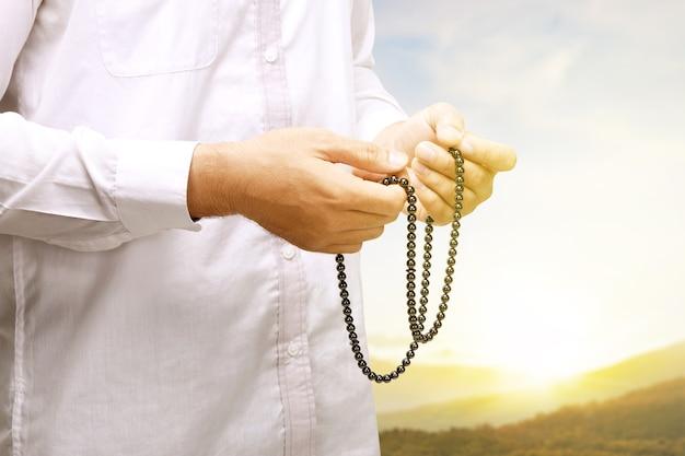 Uomo musulmano che prega con i grani di preghiera sulle sue mani