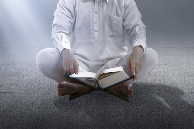 Uomo musulmano seduto e leggendo il corano sulla moschea
