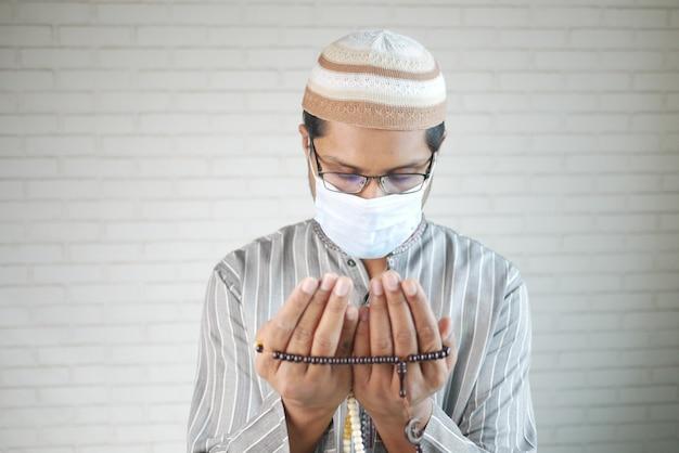 L'uomo musulmano con la maschera facciale tiene la mano nei gesti di preghiera durante il ramadan