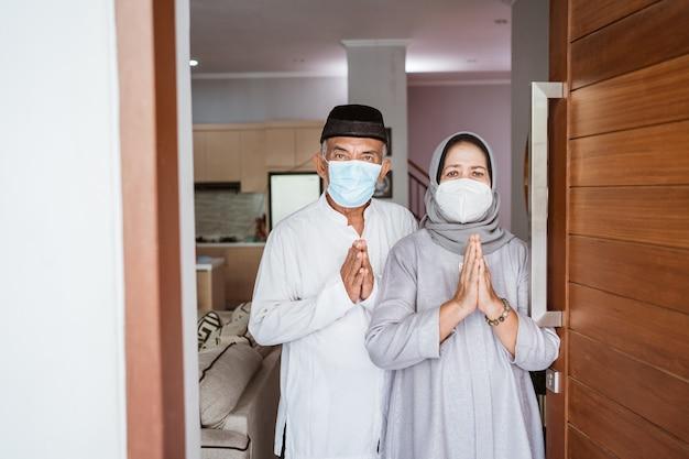 Coppia matura musulmana che indossa la maschera per il viso in piedi davanti alla porta di casa loro con gesto di saluto