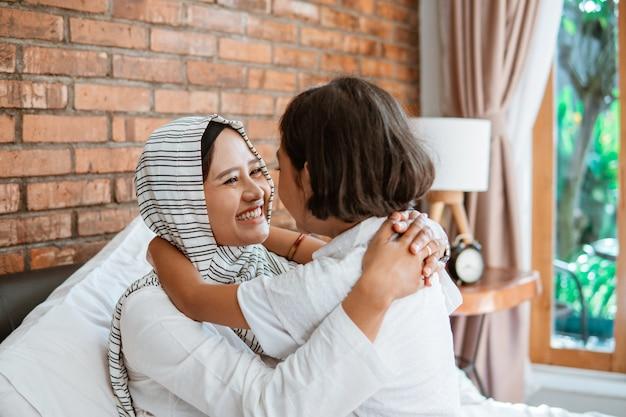 Madre musulmana che stringe a sé con sua figlia