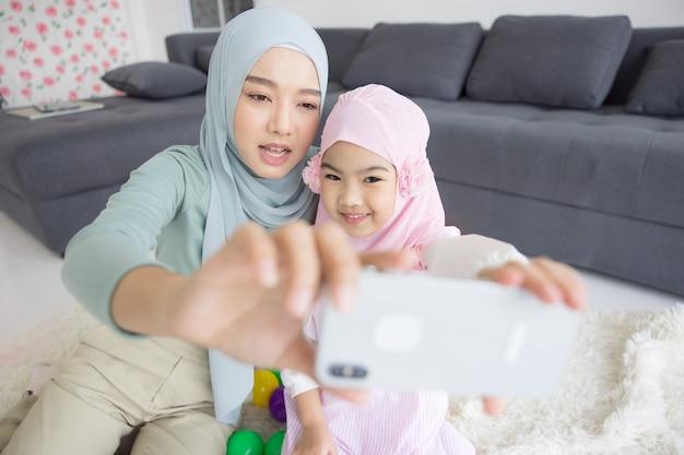 Futura maternità madre musulmana in hijab e autoritratto in salotto