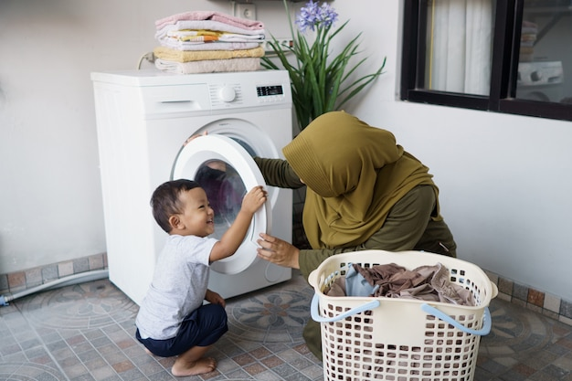 Madre musulmana una casalinga con un bambino impegnata in lavanderia con lavatrice