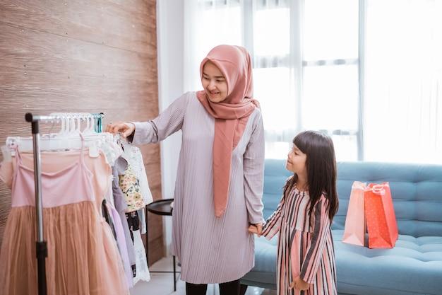 Madre musulmana che fa shopping con sua figlia in un negozio di abbigliamento boutique