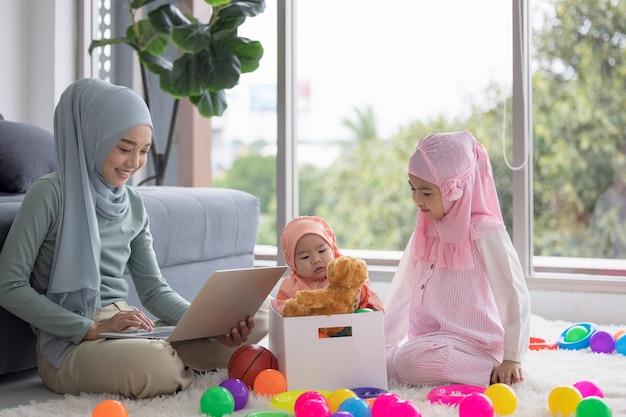 Madre musulmana che lavora con il computer portatile e il piccolo bambino sveglio che gioca i giocattoli nel salotto di casa.