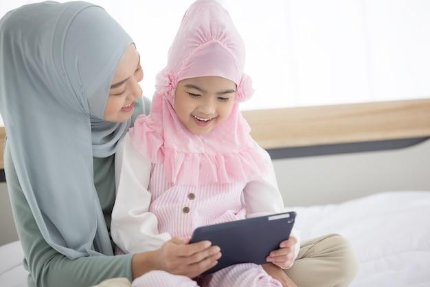 Madre musulmana che lavora con tablet e piccolo bambino sveglio a casa.