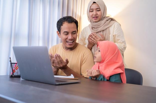 Genitore e figlia musulmani pregano insieme mentre usano il computer portatile a casa