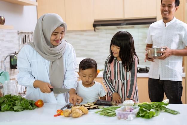 Genitori e figli musulmani si divertono a cucinare la cena iftar insieme durante il digiuno del ramadan a casa