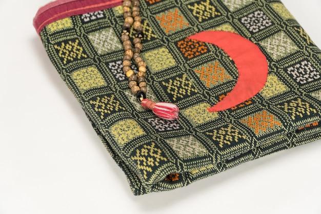 Perline di preghiera musulmane sul tappetino da preghiera con il simbolo moo su sfondo bianco