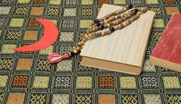 Perline di preghiera musulmane e corano sul tappetino da preghiera. concetti islamici e musulmani