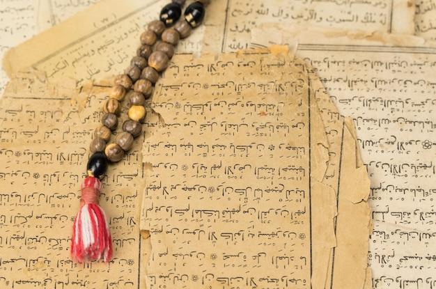 Perle di preghiera musulmane con antiche pagine del corano islamico e concetti musulmani