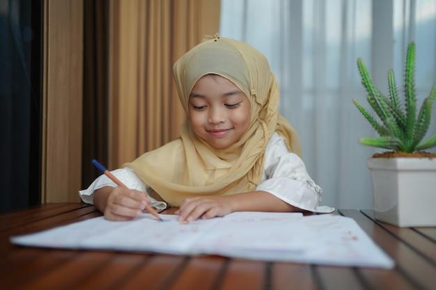 Studentessa musulmana che scrive sul libro di carta